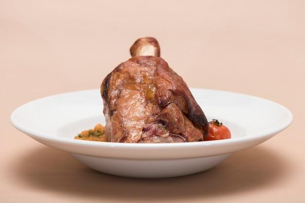 豚肉の豆、白いプレート、明るい背景、分離のナックル