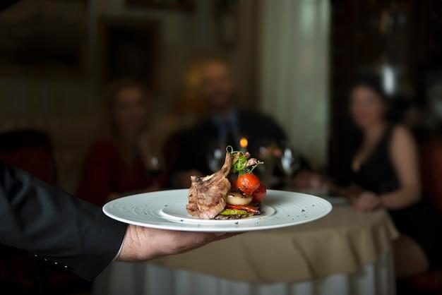 大根で飾られたグリルトマト添え美味しい子羊のグリルリブ
