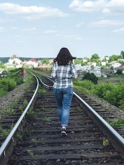 Молодая женщина в джинсах и рубашке бежит вдоль железнодорожного пути