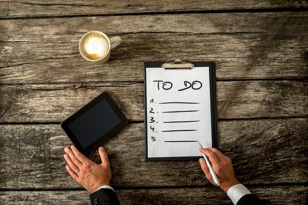 Вид сверху мужской руки, написание списка дел на белом листе бумаги