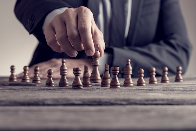 古い木製のテーブルでチェスのゲームをしているビジネスマンのレトロなスタイルのイメージ