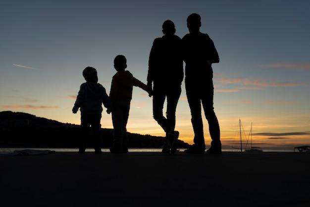 日没で野外を歩いている家族
