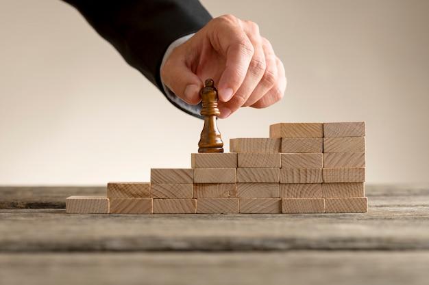 一連のステップをクイーンピースを移動するビジネスマン