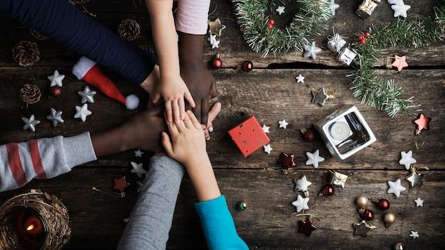 Семья смешанных рас сложа руки в обстановке рождества