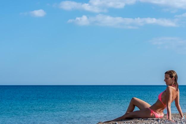 Милая молодая женщина в розовом бикини сидя на галечном пляже