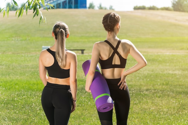 Спортсменки в парке держат в руке коврик для йоги. концепция тренировок на свежем воздухе