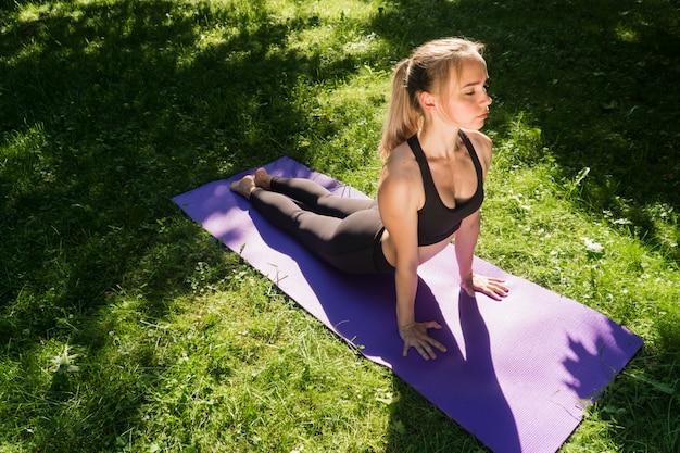 Девушка в спортивной одежде на открытом воздухе делает упражнение для похудения. йога, концепция функциональной тренировки с использованием коврика на закате