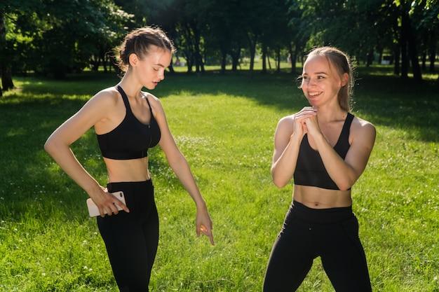 Женский фитнес-тренер занимается с клиентом на открытом воздухе. концепция социальной дистанции при силовых тренировках в парке