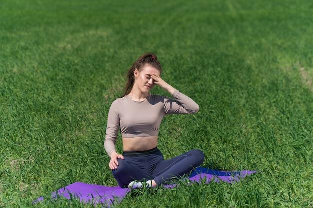 Молодая женщина упражнениями йоги на поле