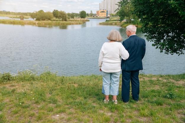 年上の男性と女性は背中を合わせて立っています