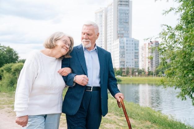 スタイリッシュな杖を持った思いやりのある老夫婦が新鮮な空気の公園を散歩します。