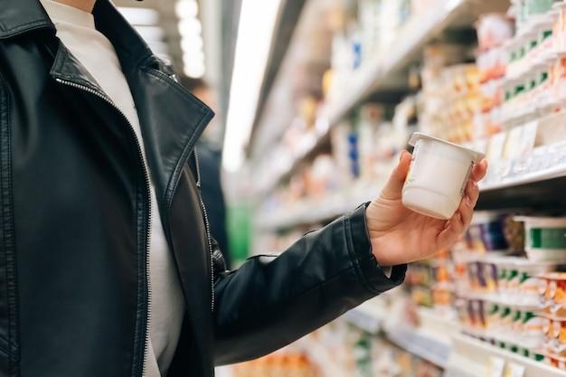 クローズアップの女性の手は店で食料品を保持しています。検疫中に大型スーパーで果物と野菜を購入する概念