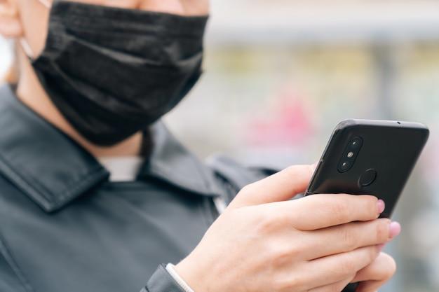 クローズアップの女性の手は、医療マスクの顔の背景に電話をかけます。安全のコンセプトはあなたの健康です。少女はタクシーを呼ぶ