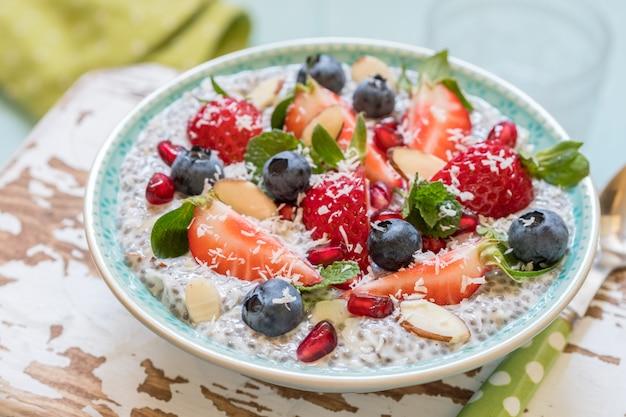 Кето кетогенная, палео низкоуглеводная диета, а не овсяная каша на завтрак. кокосовый пудинг цзя с ягодами, зернами граната и миндалем