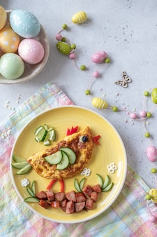 Милый омлет с куриным яйцом, ветчиной и овощами на завтрак для детей
