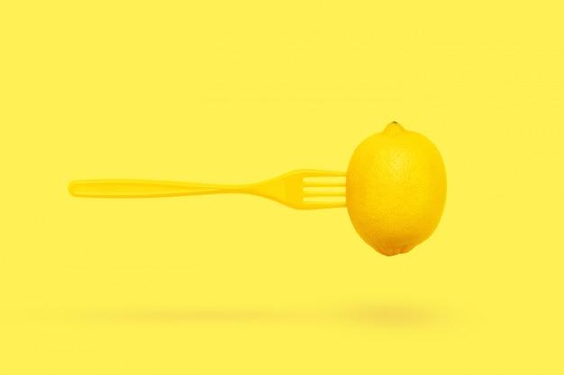 パステルイエローの背景にレモンとフォークの浮上