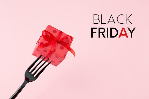 黒い金曜日のコンセプトです。黒のフォークに赤いギフトボックス