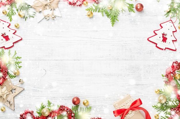 ホリデーフレーム。赤と金のクリスマスの装飾、ギフト、クリスマスライト、白いテーブルの上
