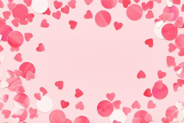 ピンクのパステル背景に赤いハートの紙吹雪のお祝いフレームは、バレンタインの日が大好きです。