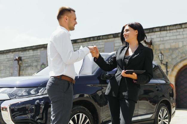 Молодой взрослый улыбающийся мужчина и женщина в деловых темных костюмах, стоя возле автомобиля рукопожатие