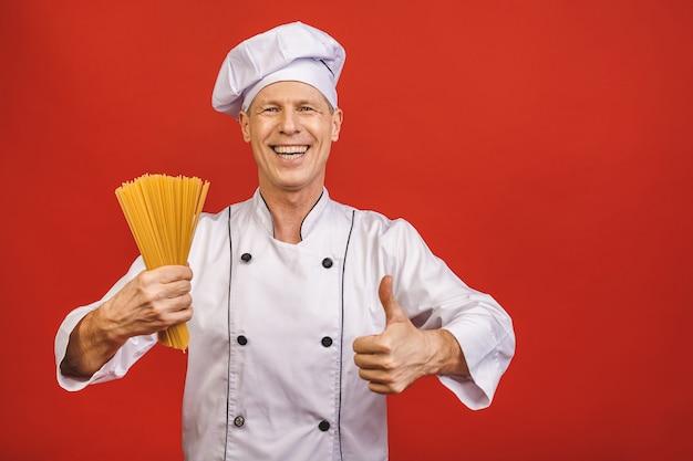 シェフは手にスパゲッティの束を保持しています。赤の背景に分離されたケータリングとイタリア料理のコンセプト。白い制服を着た満足そうな顔で料理人は親指を現して乾いたパスタを握ります。