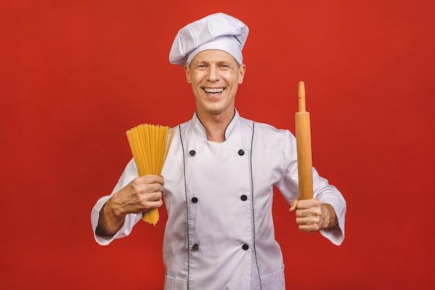 シェフは手にスパゲッティの束を保持しています。赤の背景に分離されたケータリングとイタリア料理のコンセプト。白い制服を着て満足そうな顔で料理人は乾いたパスタを握ります。