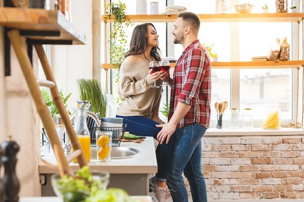 最高のレジャーは、家で一緒にリラックスすることです。自宅のキッチンに立ちながら夕食を作って美しい若いカップル。ワインを飲む。
