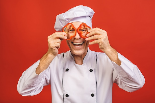 Овощные рецепты. усмехаясь человек шеф-повара держа красный сладостный перец варя еду стоя над изолированной красной предпосылкой студии.
