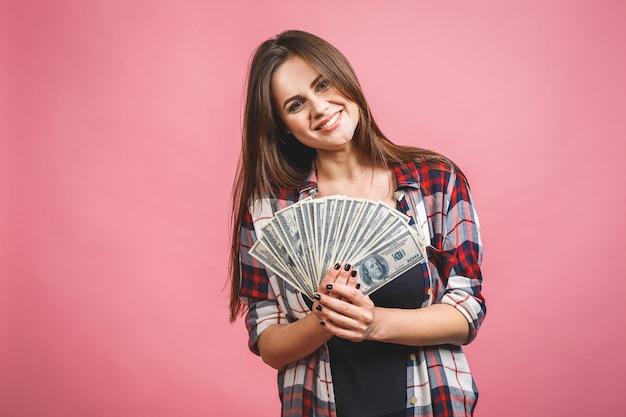 Портрет жизнерадостной молодой женщины держа банкноты денег и празднуя изолированный над розовой предпосылкой.