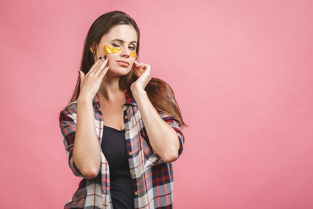 Крупный план девушки с золотыми пятнами под глазами от отеков и морщин. изолированные на розовом фоне