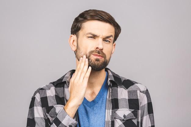 歯痛のコンセプトです。灰色の壁の上に孤立した歯の痛みの痛みに苦しんで、痛みを感じ、頬を手で持っている若い男の屋内撮影。