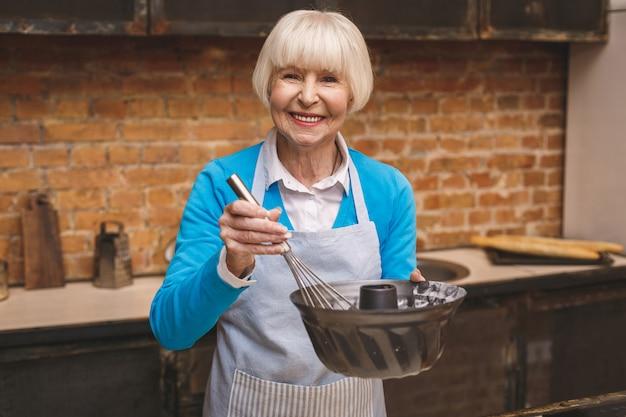 魅力的な笑顔幸せなシニア高齢女性の肖像画は、キッチンで調理しています。祖母がおいしい焼き菓子を作る。