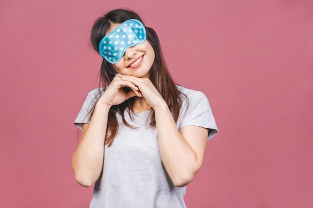 眠っているマスクで陽気な笑顔の女の子の肖像画の上半身。スタイリッシュなパジャマ立って離れている魅力的な面白い女性。ピンクの背景に分離されました。