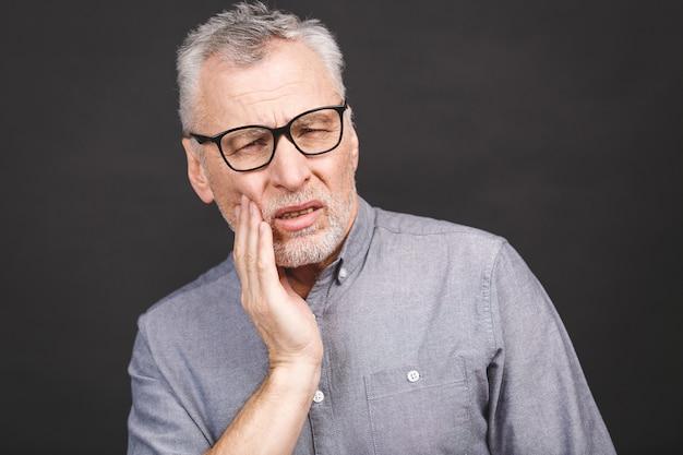 黒の背景に歯痛に苦しんでいる年配の男性のクローズアップの肖像画。
