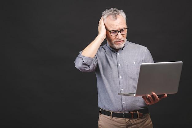 行うにはあまりにも多くの仕事。ラップトップコンピューターで疲れている怒っているシニア高齢男性