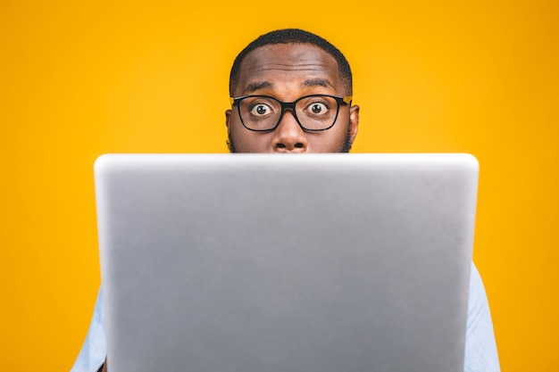 Молодой человек удивил афроамериканца стоя и используя портативный компьютер