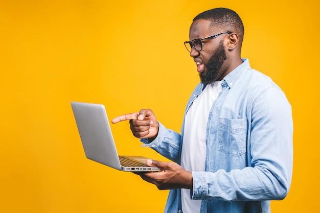 Молодой человек удивлен, стоя и с помощью портативного компьютера