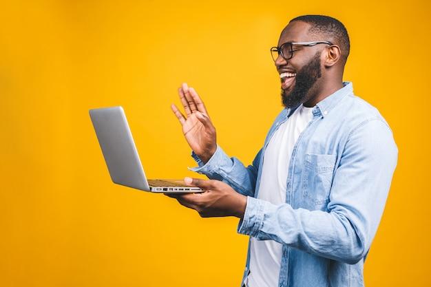 Молодой счастливый усмехаясь афро-американский человек стоя и используя портативный компьютер