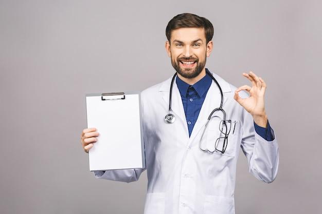 空の紙でクリップボードを保持しているひげを生やした笑顔のインターンの肖像画。医者は白い制服を着て、孤立した灰色の背景の上に立って、空白を示します。
