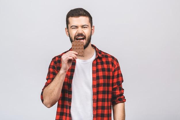 Молодой красивый человек ест шоколад, изолированные на белом фоне с счастливым лицом, стоя и улыбка с уверенной улыбкой, показывая зубы.