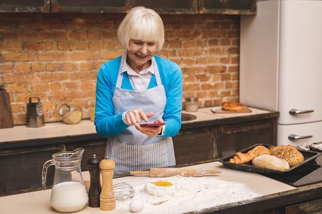 魅力的な年配の女性はキッチンで調理しています。祖母がおいしい焼き菓子を作る。電話を使用して。
