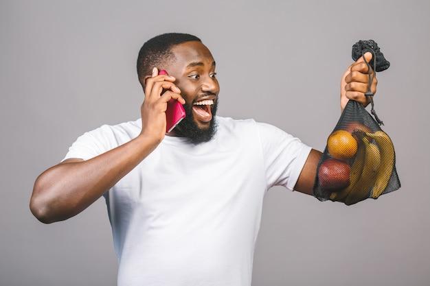 Афро-американских чернокожих мужчин держит сетка мешок с продуктами без пластиковой упаковки, изолированные на сером фоне. с помощью телефона.