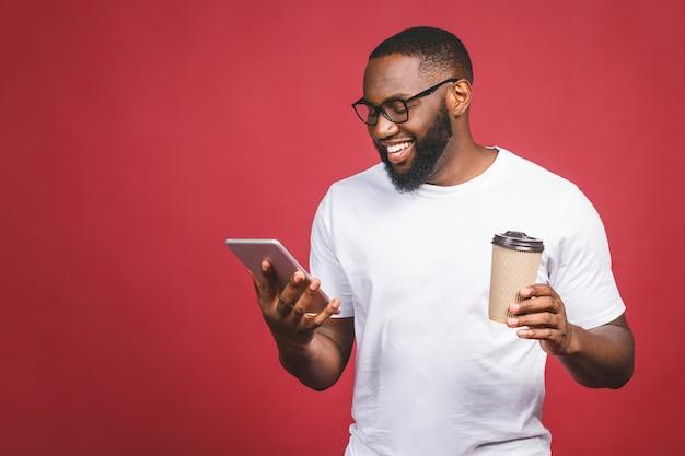 Печатать сообщение жизнерадостный чернокожий человек печатая что-то на мобильном телефоне, выпивая кофе и усмехаясь пока стоящ изолированный против красной предпосылки.
