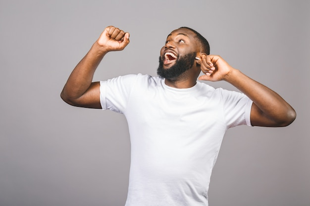 クールな音楽を聴く。若い陽気なアフリカ系アメリカ人の黒人男性が灰色の背景に分離されたダンスを移動します。