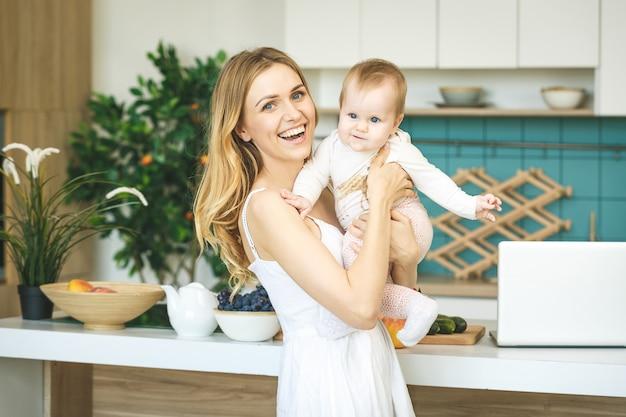 Молодая мать смотрит на камеру и улыбается, готовить и играть с дочерью младенца в современной кухне. с помощью телефона.