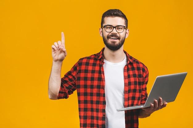 Молодой бородатый человек держит ноутбук и палец вверх.