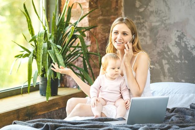 Мать и ее маленький ребенок дома. мать с ребенком смотреть что-то на ноутбуке. работаю дома. с помощью телефона.