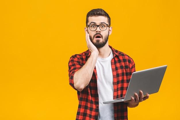 Портрет изумленного человека держа портативный компьютер
