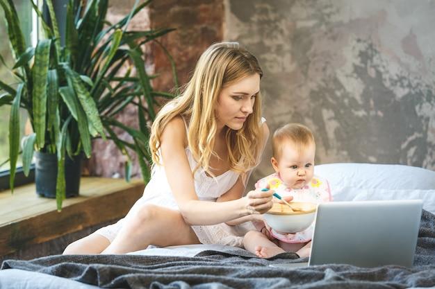 スプーンで女の赤ちゃんを授乳する母親。母は家で彼女の愛らしい子供に食べ物を与えます。