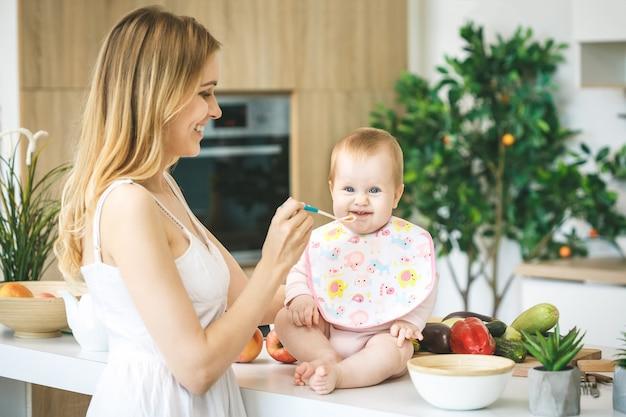 スプーンで女の赤ちゃんを授乳する母親。母は家で彼女の愛らしい子供に食べ物を与えます。ベビーフード